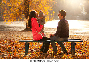 Family having fun at autumn park on bench near river - Young...