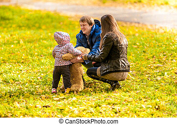 Family playing with daughter and teddy bear at park - Young...