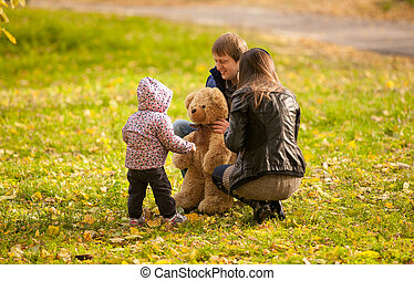 Girl playing with teddy bear and parents at park - Small...
