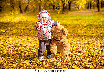 girl walking with teddy bear at autumn park - Little girl...