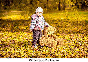 smiling girl holding teddy bear at autumn park - Small...