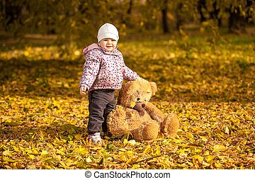 Girl in pink coat holding big teddy bear at park - Small...