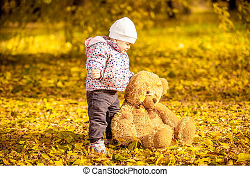 Girl playing with teddy bear at autumn park - Portrait of...