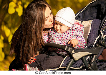 portrait of mother kissing daughter in buggy - Closeup...