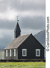 Cloudy sky, dark church in Budir, Iceland - Rear view of...