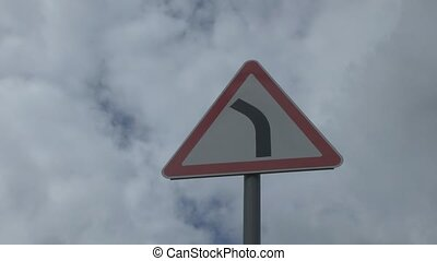 Road sign on background clouds - The camcorder is moving...