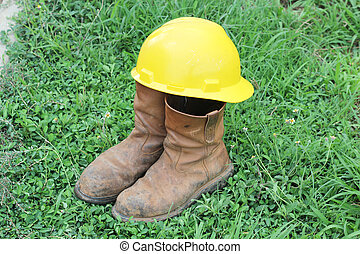 Old brown work boots and hard hat on green grass