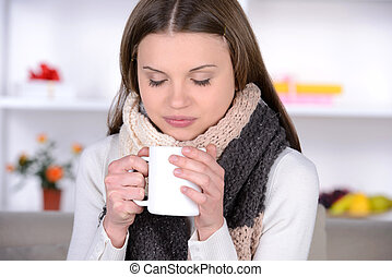 Medicine - Drinking hot tea. Young woman in scurf drinking...