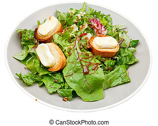 green salad with goat cheese on plate isolated on white...