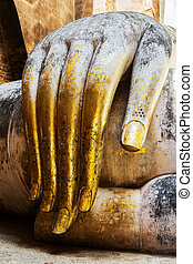 gold leaf offerings on slender fingers of wat si chums...