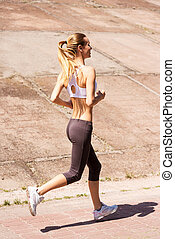Enjoying her daily jog. Side view of young woman running...