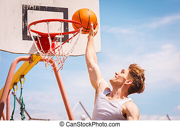 Slam Dunk Side view of young basketball player making slam...