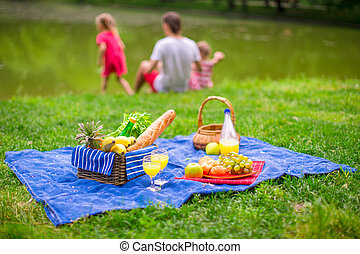 Family picnicking - Father with little daughters on picnic...