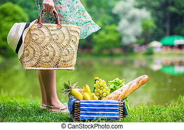 Picnic basket with fruits, bread and hat on straw bag near...