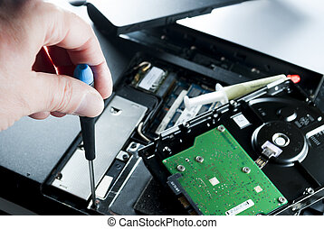 man fixing computer or laptop or notebook with crewdriver
