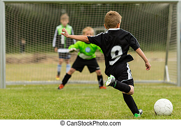 Kids soccer penalty kick - Goalkeeper and penalty kicker in...