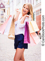 Shopping therapy. Beautiful young cheerful woman holding...