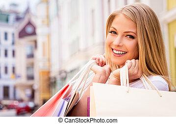 Happy shopaholic girl. Beautiful young cheerful woman...
