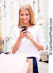 Sharing good news with friend. Close-up of beautiful young smiling woman holding shopping bags and mobile phone while standing outdoors