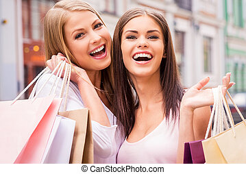 We love shopping together. Two happy young women holding shopping bags and smiling while standing outdoors