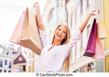 Shopping makes her happy. Attractive young woman holding...