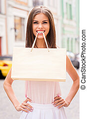 Shopping is fun! Beautiful young woman carrying shopping bag...