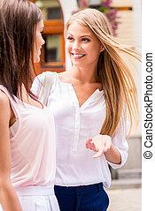 Friendly talk. Two beautiful young women walking along the...