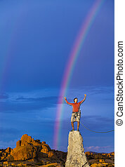Climber on the edge. - Climber celebrates on the summit of a...