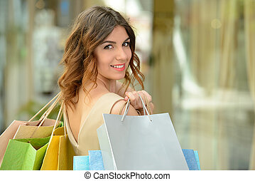 Shopping - Woman shopping. Beautiful young woman shopping in...