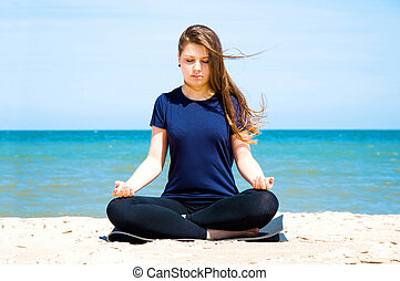 Mental health. Young woman practicing yoga at sea.