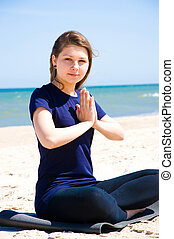 Mental health Young woman practicing yoga at sea