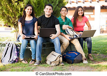 Happy students using technolgy - Group of high school...