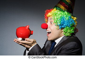 Clown with piggybank in funny concept