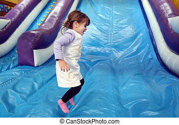 Little girl plays on Inflatable giant slide - Little girl...