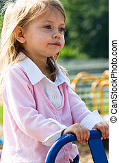 girl playing  - a little girl playing on a teeter totter