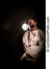 Crazy person in a cell wearing a straitjacket