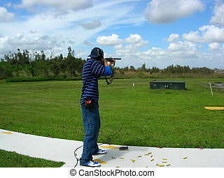 Man Trap Shooting - Man shooting trap targets at an outdoor...