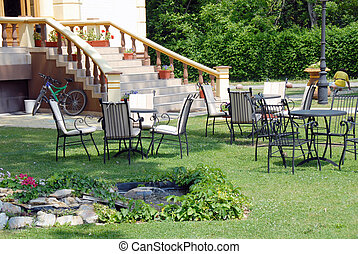 Home yard - house stairs with flowerpots and tables on lawn...