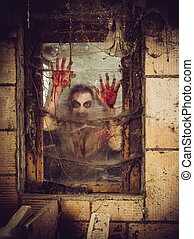 Bloody zombie at the window - Photo of a zombie outside a...