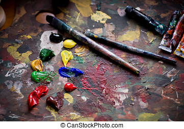 Painters brushes and old pallet with multiple vibrant colors...