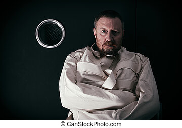 Insane man in a cell wearing a straitjacket - Photo of an...