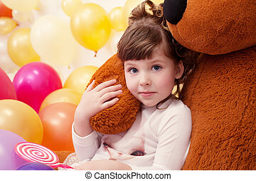 Portrait of lovely little girl hugging teddy bear, close-up