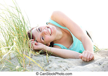 Carefree young woman lying on beach - Close up portrait of a...