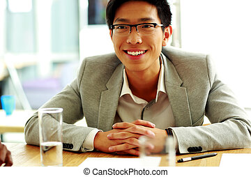 Happy asian man sitting at the table in office