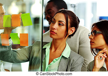 Beautiful businesswoman writes notes in the office