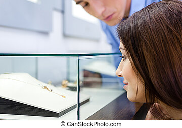 Girl with man selects expensive jewelry at jeweler's shop....