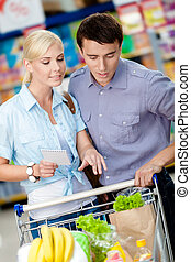 Couple discussing the shopping list and chosen products