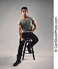 Handsome young man sitting on bar stool - Full length...