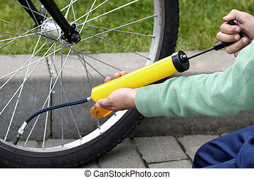Pumping bicycle tire - Boy pumping his bicycle tyre,...