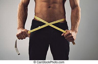 Fitness man measuring his waist - Fitness man measuring his...